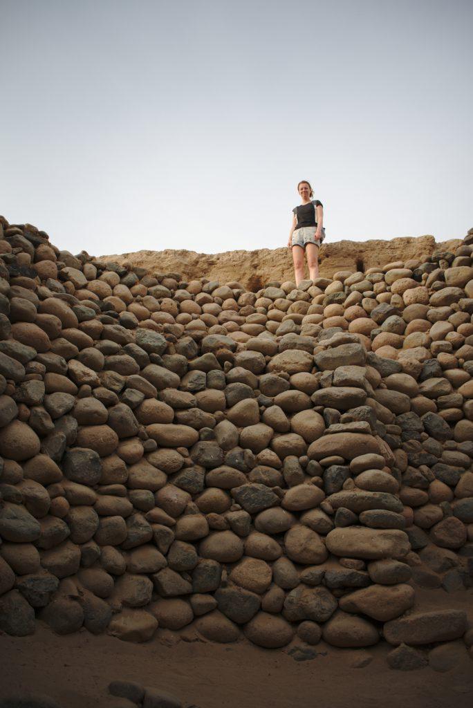 Von unten nach oben aus einem Äquadukt fotografiert. Lisa steht am Rande des Äquadukts aus Steinen und schaut in die Kamera.