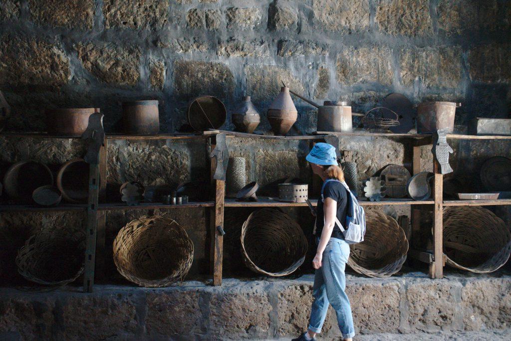 Eine Steinwand, davor ist ein Holzregal mit vielen Kochtöpfen und Körben. Lisa steht davor und schaut sie sich an. Sie trägt einen blauen Hut und einen Rucksack.